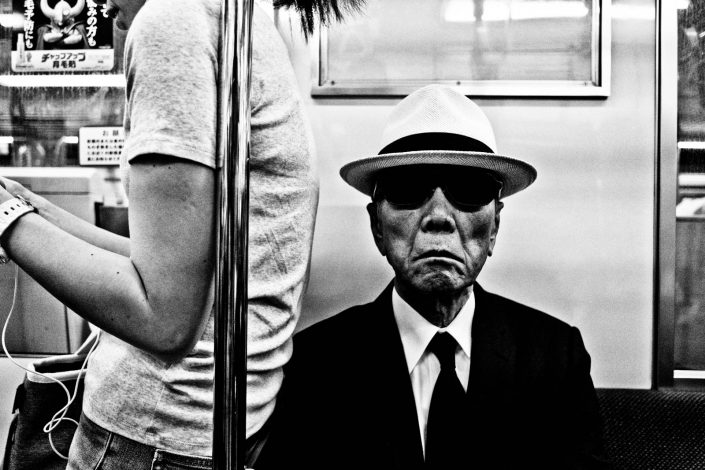 Cool old man with sunglasses and hat in a metro of Tokyo, Japan. Street Photography by Victor Borst