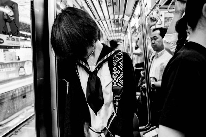 Japanese girl in metro with hair in front of her face totally secluded from her surroundings. Street photography by Victor Borst
