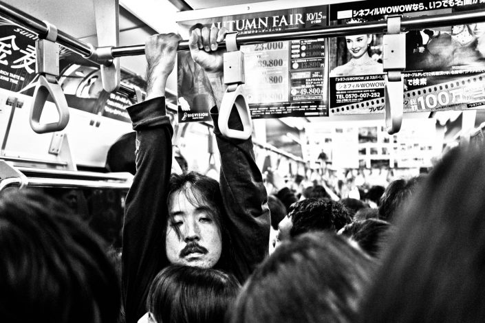 Japanese man hanging in a metro in Tokyo tired and in a crowd. Street Photography by Victor Borst