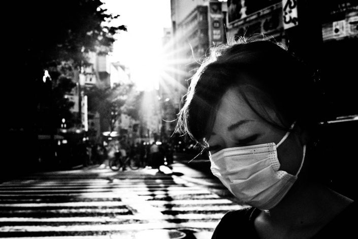 Japanese woman with facemask with low sunlight on Shibuya, Tokyo. Street Photography by Victor Borst