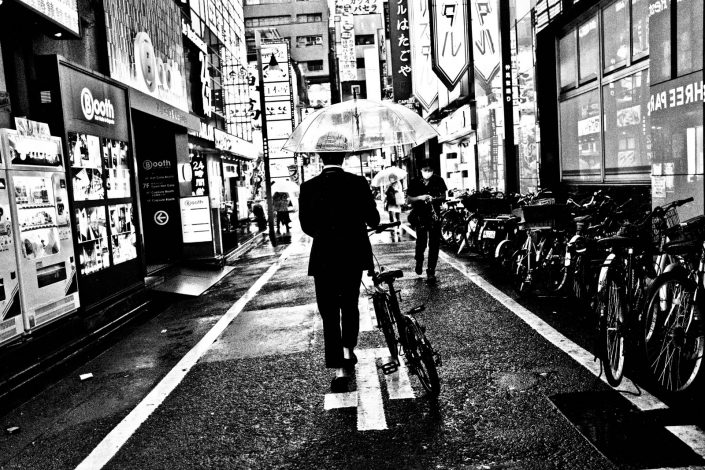 Shinjuku in the rain, Japanese man with bike and umbrella. Street Photography by Victor Borst