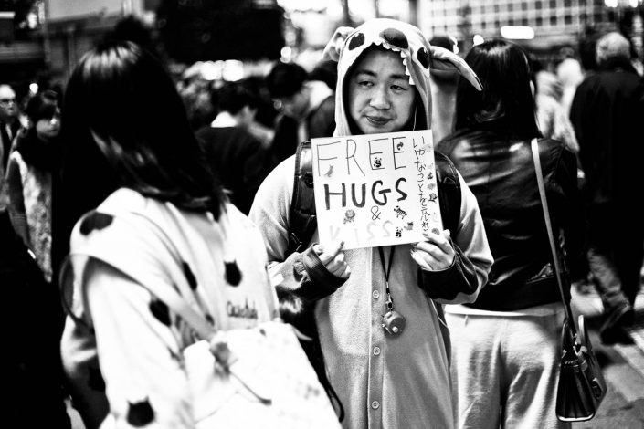 Cosplay Japanese guy with a sign Free hugs & kiss at Shibuya, Tokyo. Street Photography by Victor Borst