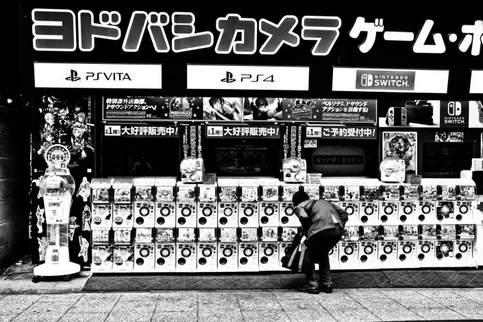 A Japanese man trying to get a toy out of a Gashapon machine. Street photography by Victor Borst