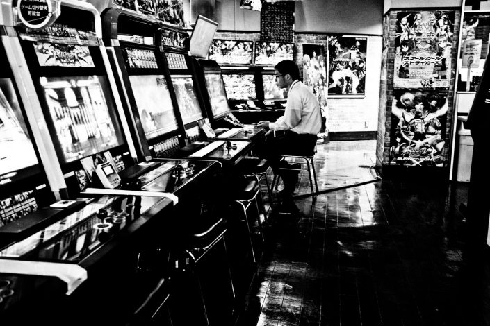 Japanese man playing an Arcade game in Akihabara, Tokyo. Street photography by Victor Borst