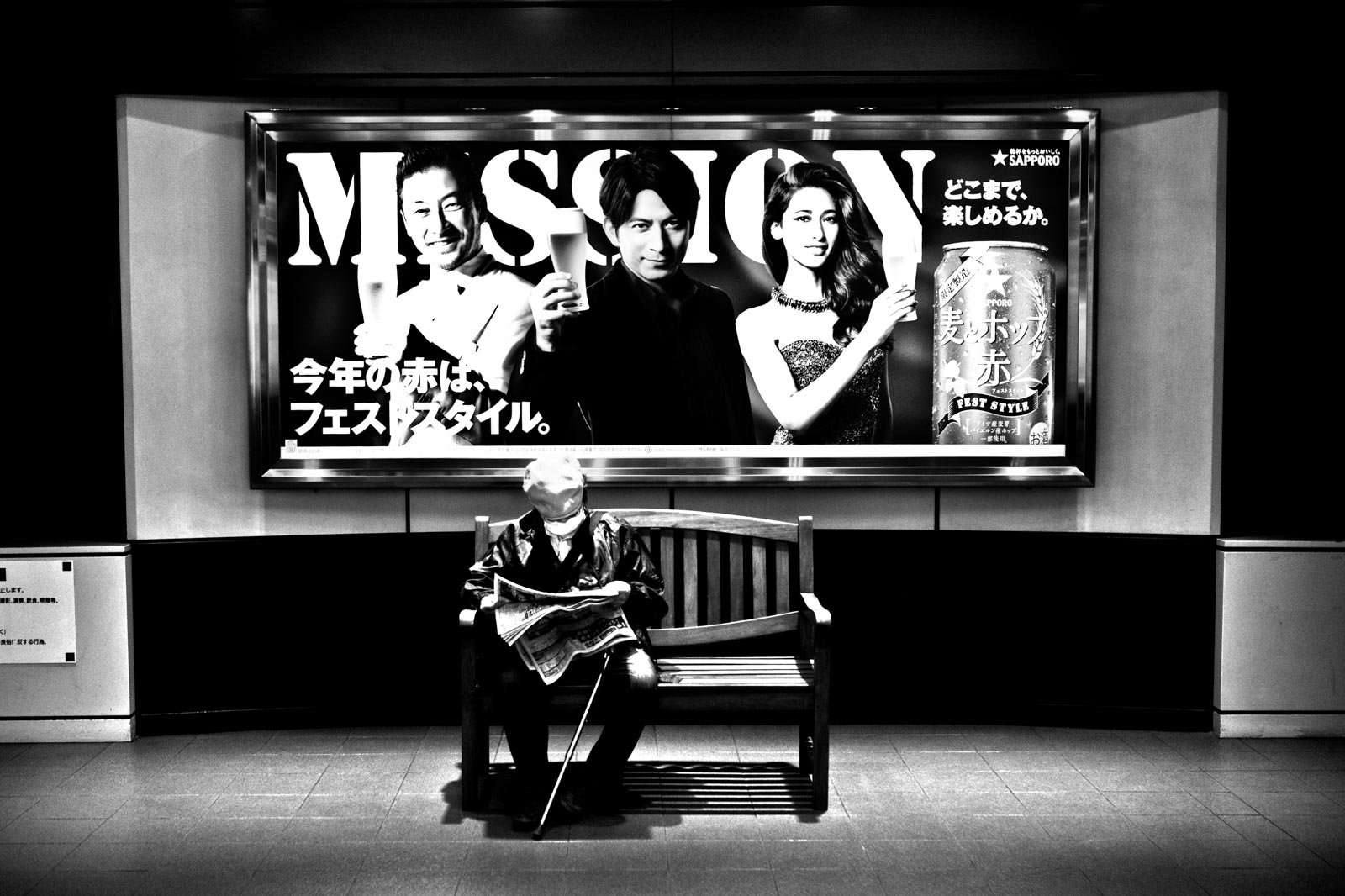 Old Japanese man sitting and reading a newspaper under a flashy billboard. Street photography by Victor Borst