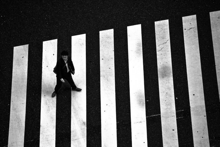 Japanese man crossing a crossover totally in monochrome. Street photography by Victor Borst