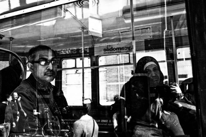 Window picture of people riding a bus in Antwerp with reflections. Street Photography by Victor Borst