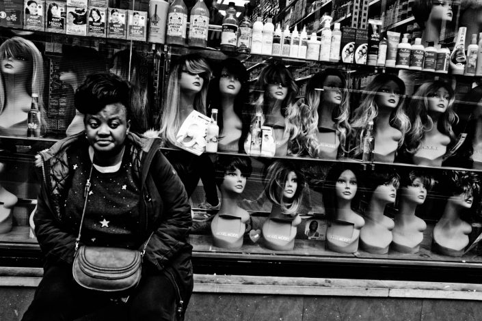 Portrait of an African woman in Brussels with a lot of faces with wigs. Street photography by victor borst