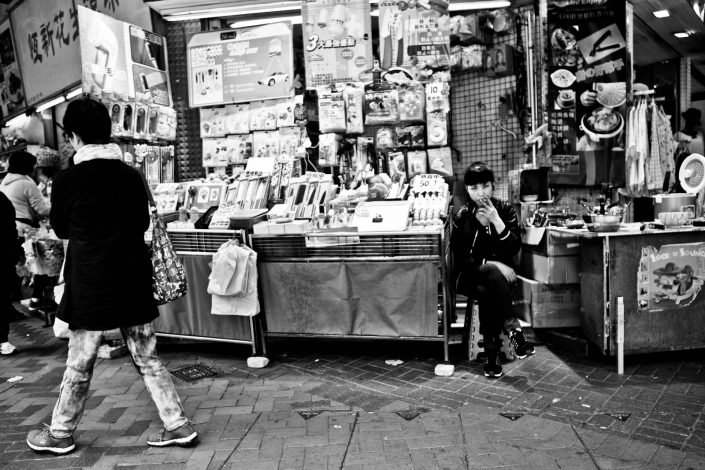Smoking girl at a shop in Hong Kong. She looks a bit mean. Street Photography by Victor Borst