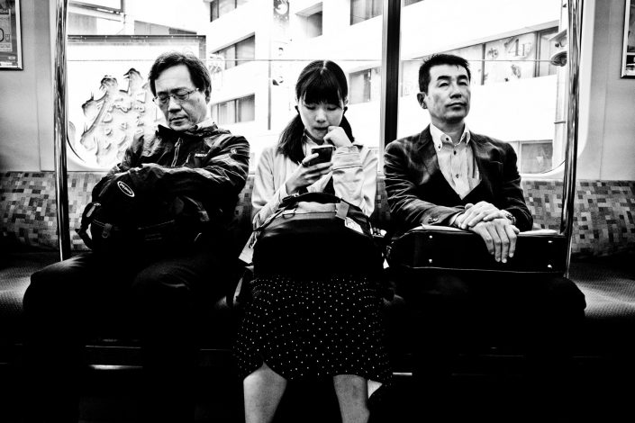 In the metro of tokyo. A girl is playing with her smartphone, one guy is sleeping and one notice me. Street photography by Victor Borst