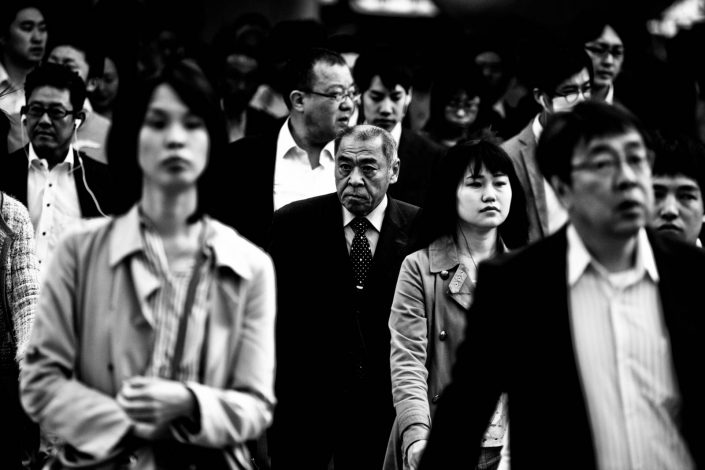 Portrait of an old man within a crowd at Shimbashi station. Street Photography by Victor Borst