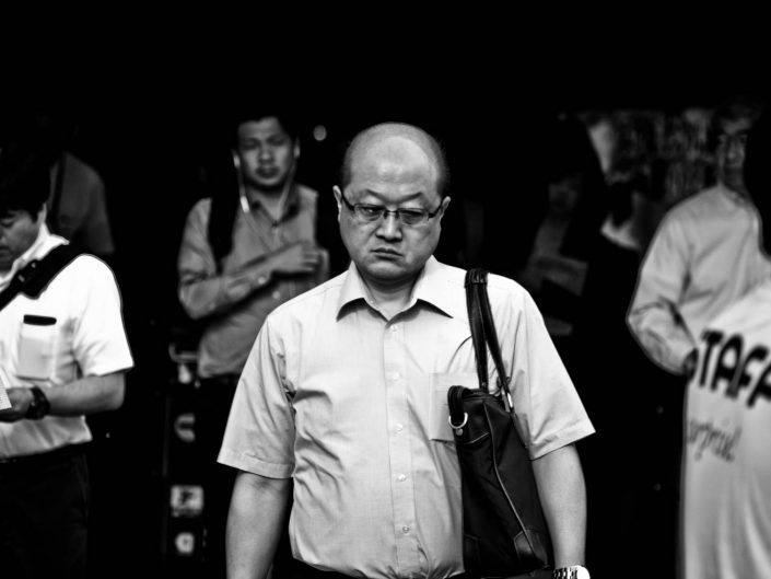 Bald men with glasses at Shimbashi station of to work. Street Photography by Victor Borst