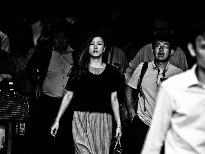 Beautiful woman between salarymen at Shimbashi station. Street Photography by Victor Borst