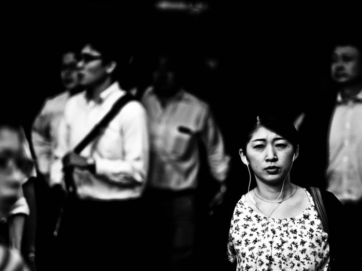 Salary woman with headphones listening to music at Shimbashi station. Street Photography by Victor Borst