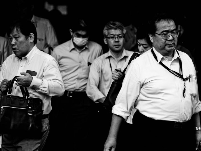 Big group of salarymen at Shimbashi station. Nobody looks into the camera. Street Photography by Victor Borst