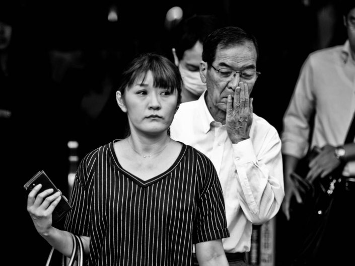 Salaryman and woman portrait. Woman with smartphone, man with hand in front of his mouth. Street Photography by Victor Borst