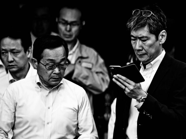 Man looking at his smartphone with glasses in his head in a Shimbashi crowd. Street Photography by Victor Borst