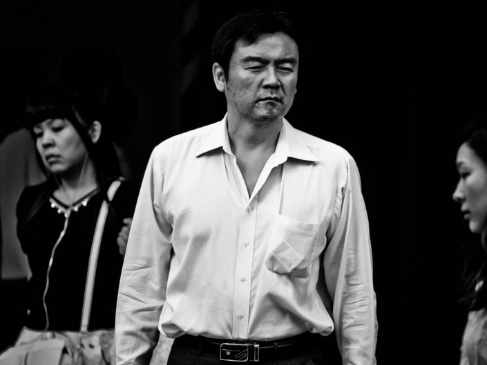Sick looking salaryman at Shimbashi station, Tokyo. Street Photography by Victor Borst