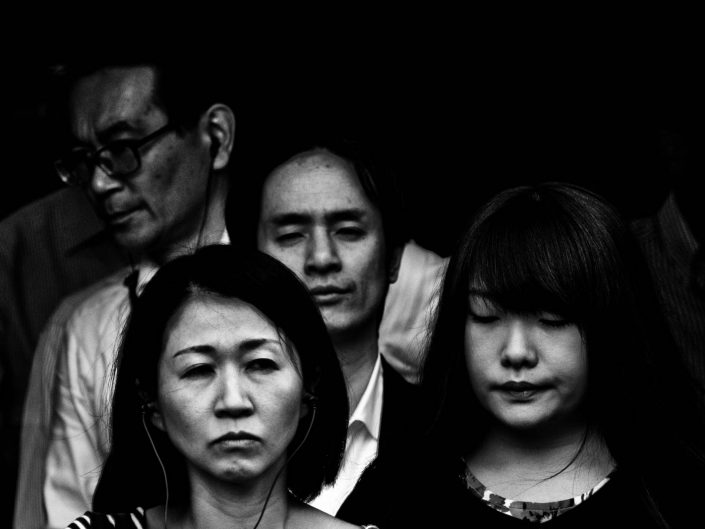 Close up faces of salarymen and women at Shimbashi station. Street Photography by Victor Borst