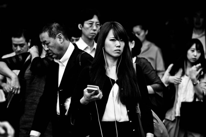 Lots of faces at Shimbashi station with the focus on one woman listening to music. Street Photography by Victor Borst