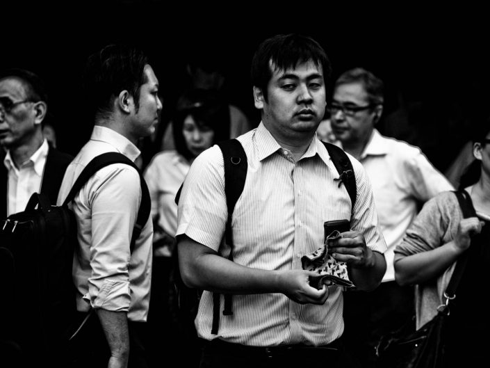 Some salarymen and women at Shimbashi station, one with a handkerchief. Street Photography by Victor Borst