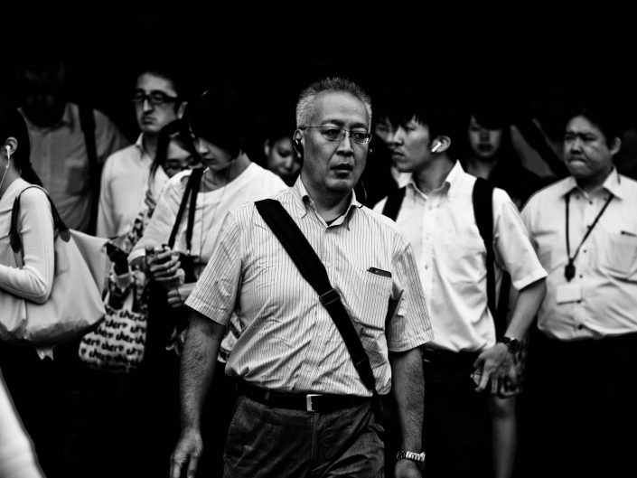A crowd of salarymen and women all heading to work on a warm day. Street Photography by Victor Borst