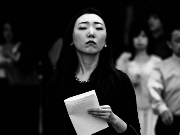 strict looking woman with a paper in her hand going to work at Shimbashi station. Street Photography by Victor Borst