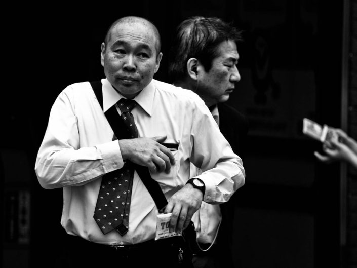 Two faces at Shimbashi station, one bald, one with closed eye including a pair of hands. Street Photography by Victor Borst