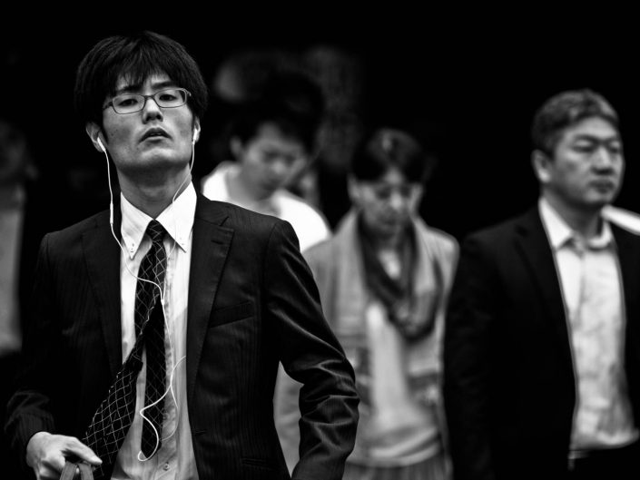 Portrait of a salaryman listening to some music with glasses. Street Photography by Victor Borst