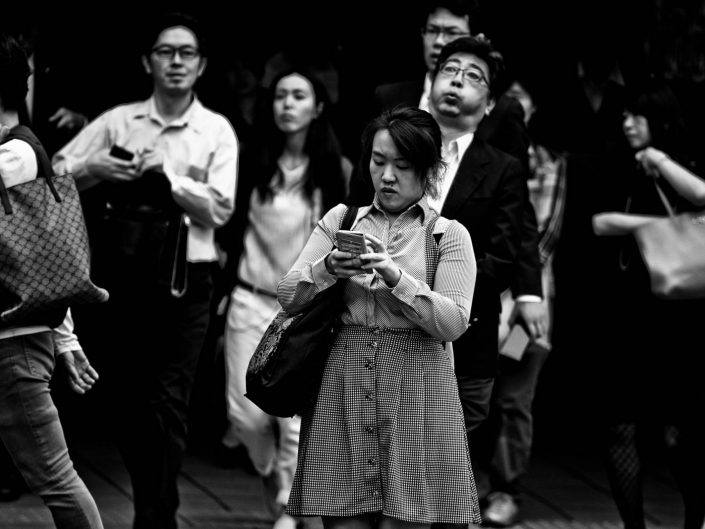 Portrait of a salaryman and woman. One puffing and one on the phone. Street Photography by Victor Borst