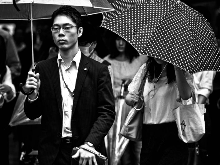 Portrait of a salaryman with umbrella and a woman with umbrella with dots. Street Photography by Victor Borst