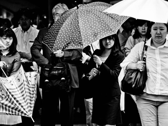 Umbrella people exiting Shimbashi station. Street Photography by Victor Borst