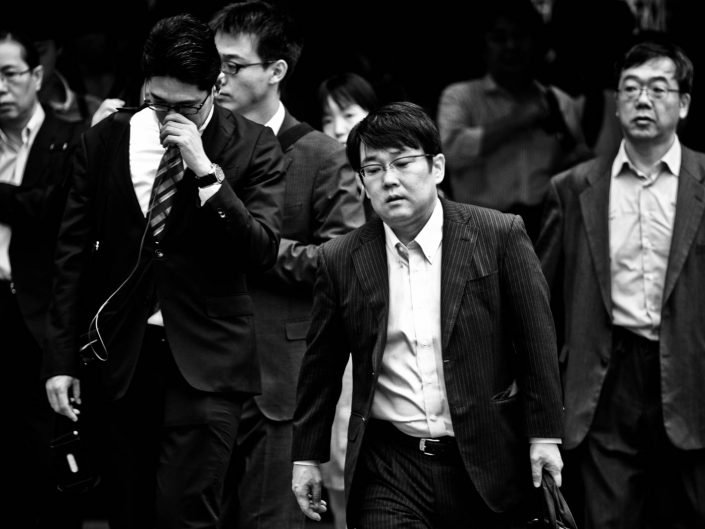 Group of salarymen in suits at shimbashi station heading for work. Street Photography by Victor Borst