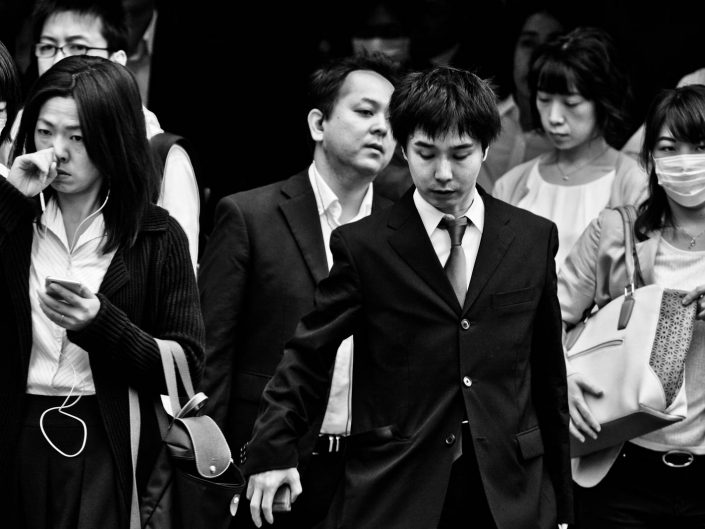 Group of salarymen and women at shimbashi station one with mask, one touching nose. Street Photography by Victor Borst