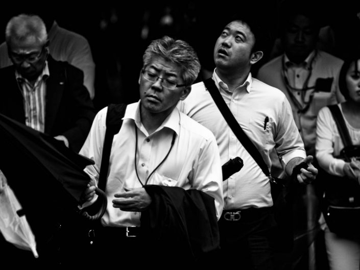 Salarymen exiting Shimbashi station watching for the rain with umbrella. Street Photography by Victor Borst