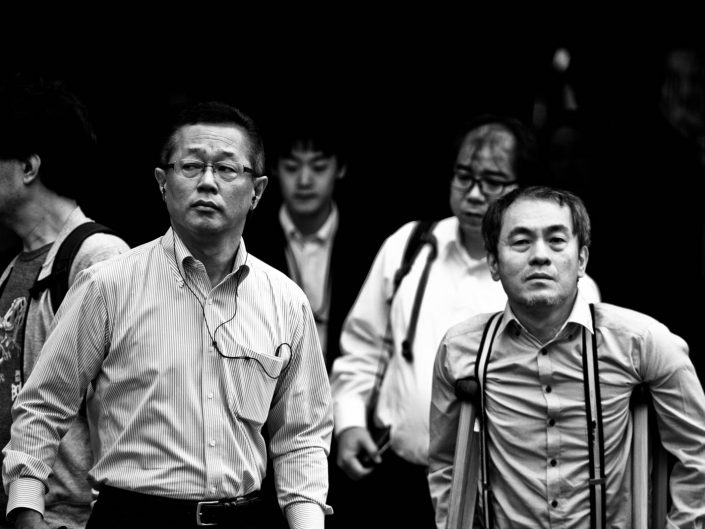 Two salarymen, one with glasses and one with crutches. Street Photography by Victor Borst