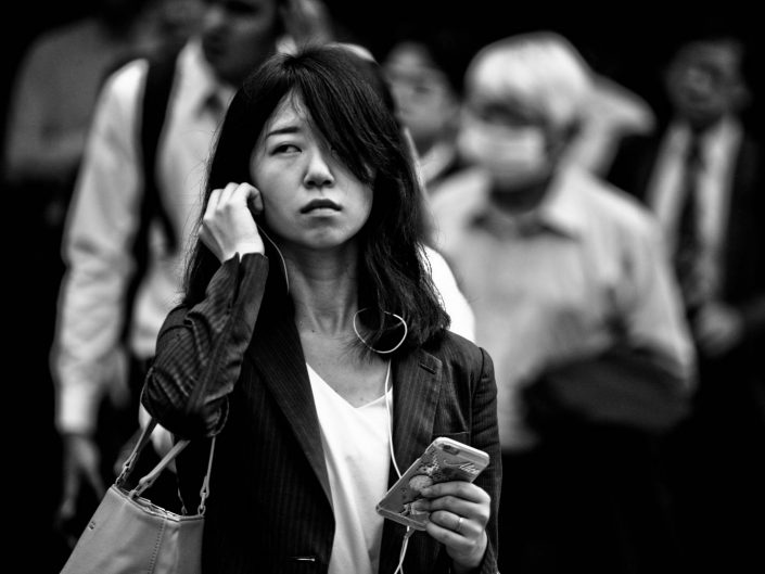 Portrait of an japanese woman at shimbashi station, listening to music on smartphone. Street Photography by Victor Borst