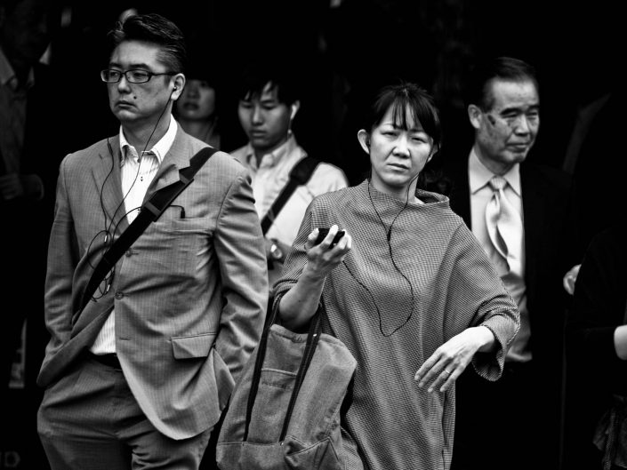 One Japanese woman and on man listening on headphones to music on their way to work. Street Photography by Victor Borst