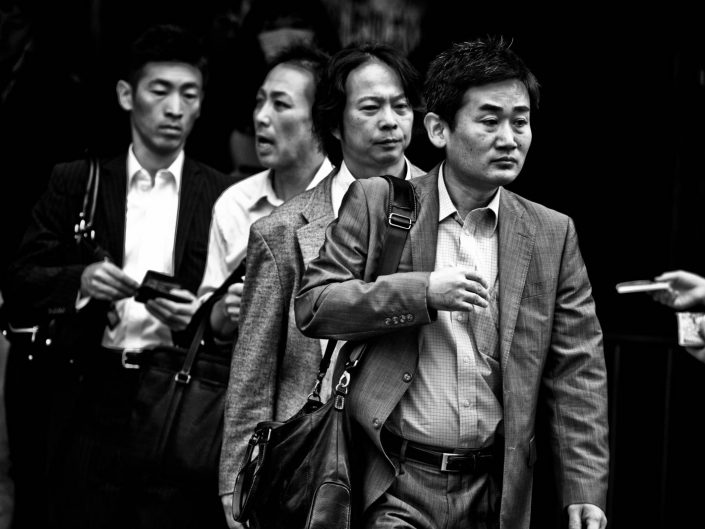 Four salarymen in a row at Shimbashi station going to work. Street Photography by Victor Borst