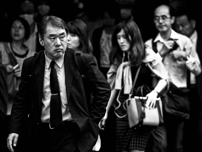 Japanese man looking to his right in a crowd at Shimbashi Station. Street Photography by Victor Borst