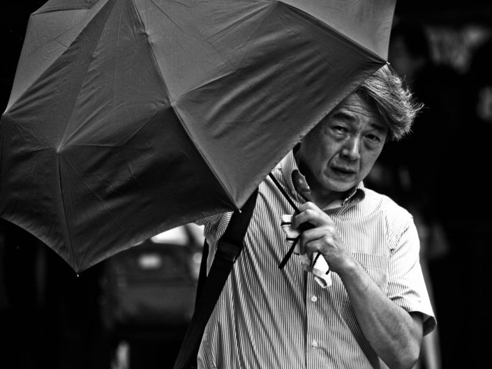 Portrait of a salarymen with an umbrella at Shimbashi Station. Street Photography by Victor Borst