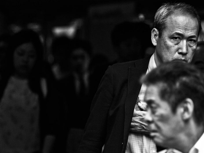 Two faces of salarymen just in the frame at Shimbashi Station. Street Photography by Victor Borst