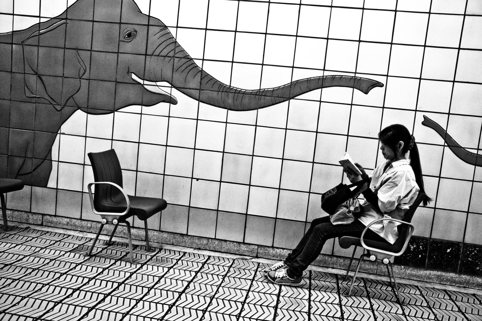 Woman sitting in the metro system of Osaka next to a mural of a elephant. Street Photography by Victor Borst