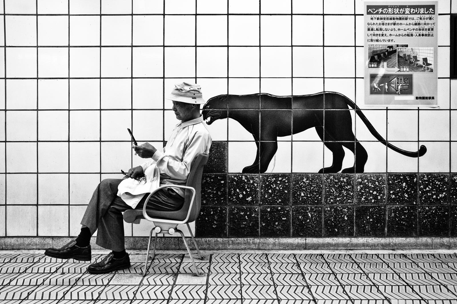 Man sitting in the metro system of Osaka next to a mural of a black panther. Street Photography by Victor Borst