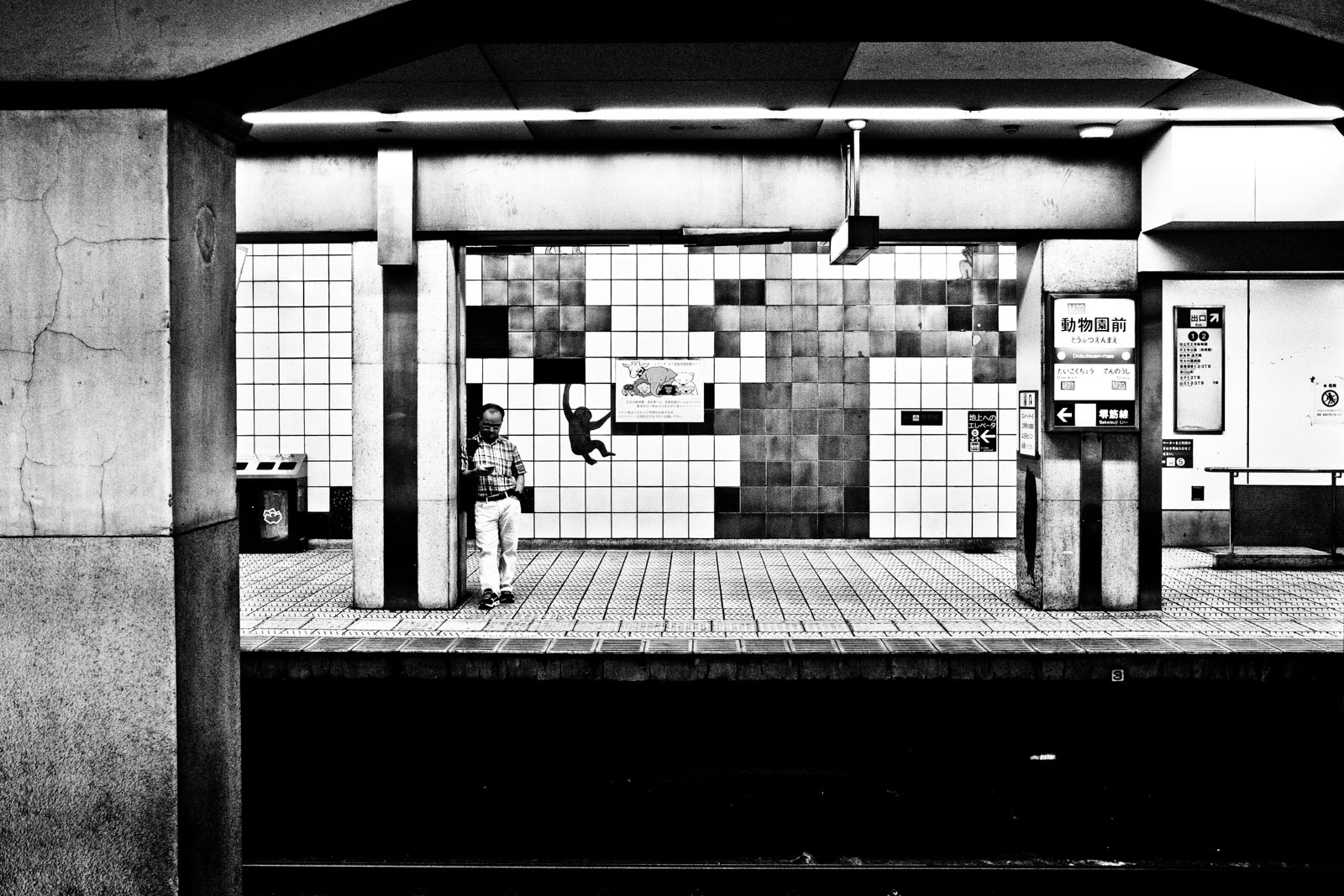 Man standing in the metro system of Osaka next to a mural of a monkey. Street Photography by Victor Borst