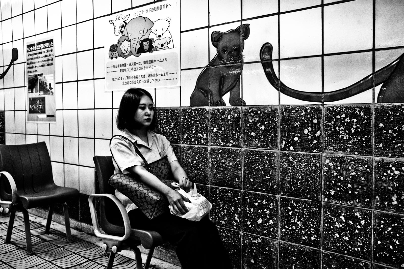 Woman sitting in the metro system of Osaka next to a mural of cub lion. Street Photography by Victor Borst