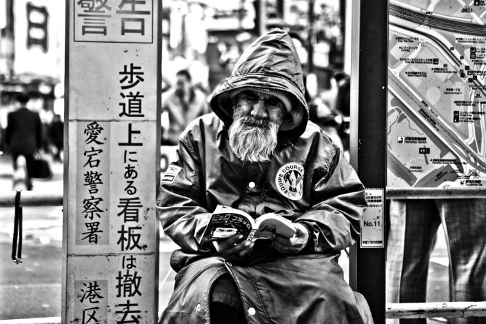 Japanese Homeless at Shimbashi Station, Tokyo. He is reading a manga. Street Photography by Victor Borst