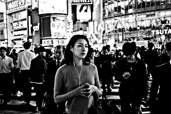 Japanese woman at Shibuya secluded from the crowd. Street Photography by Victor Borst