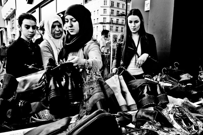 Four ladies doing some shoe shopping hunting for a bargain. Street photography by Victor Borst.