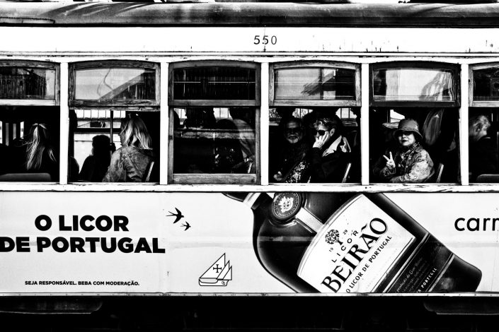 A woman giving me the peace sign sitting in a little tram in Lisboa. Street Photography by Victor Borst.